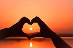在心脏形状手之间的日出视图 免版税图库摄影