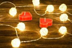 在心脏形状的两个蜡烛在发光的灯笼中的由藤条制成在木背景 侧视图,特写镜头 图库摄影