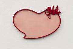 在心脏形状的华伦泰框架与丘比特的 库存照片