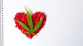 在心脏形状的大麻叶子在笔记本 免版税图库摄影