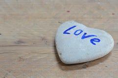 在心脏形状的岩石在木板 库存图片