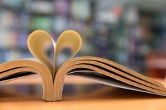 在心脏形状的旧书页有图书馆背景,在VA的爱 免版税库存照片