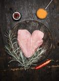 在心脏形状的未加工的鸡胸脯用草本和香料在黑暗的木背景,顶视图 库存照片