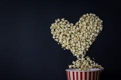 在心脏形状的玉米花在黑背景 电影恋人 免版税图库摄影