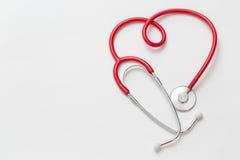 在心脏形状的红色听诊器在白色背景的 图库摄影