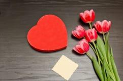 在心脏形状的红色箱子,干净的卡片,桃红色郁金香 黑色表 顶视图,文本的空间 免版税库存图片