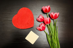 在心脏形状的红色箱子,干净的卡片,桃红色郁金香 黑色表 顶视图,文本的空间 免版税库存照片