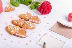 在心脏形状的自创曲奇饼与我爱你词的作为恋人的礼物在华伦泰` s天 与招呼的c的白色木桌 库存图片
