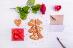 在心脏形状的自创曲奇饼与我爱你词的作为恋人的礼物在华伦泰` s天 与招呼的c的白色木桌 免版税库存照片