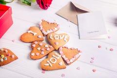 在心脏形状的自创曲奇饼与我爱你词的作为恋人的礼物在华伦泰` s天 与招呼的c的白色木桌 免版税库存图片