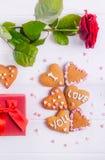 在心脏形状的自创曲奇饼与我爱你词的作为恋人的礼物在华伦泰` s天 与招呼的c的白色木桌 库存照片