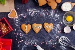 在心脏形状的自创曲奇饼与我爱你词的作为恋人的礼物在华伦泰` s天 与ingredi的黑暗的石背景 免版税库存图片