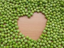 在心脏形状的豌豆在木背景 库存照片