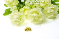 在心脏形状的金下垂有浮雕的贝壳耳环首饰与花我 库存图片