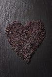 在心脏形状的黑米在与水滴的黑石背景 免版税库存图片