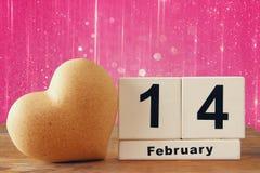 在心脏旁边的2月14日木葡萄酒日历在木桌上 闪烁背景 被过滤的葡萄酒 免版税库存照片