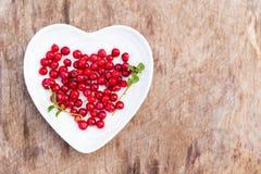 在心脏板材的新鲜的红色森林蔓越桔在木背景 图库摄影