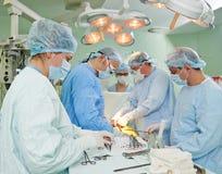 在心脏病手术操作的外科医生队 图库摄影