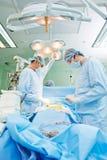 在心脏病手术操作的外科医生队 库存照片