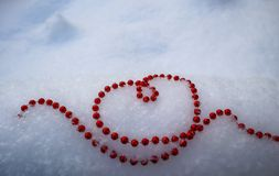 在心脏的形状的明亮的红色小珠在新鲜的白雪的 完善的情人节,圣诞节,新年贺卡背景 图库摄影