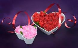 在心脏的玫瑰塑造有红色丝带的碗 库存照片