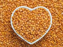 在心脏碗的红色橙色扁豆橄榄球在扁豆背景 免版税库存图片