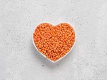 在心脏碗的红色橙色扁豆橄榄球在灰色水泥背景 免版税库存照片
