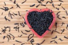 在心脏碗的黑茶叶 免版税库存图片