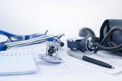 在心脏科医师Tonometer,心电图和笔记薄的工作表上的听诊器与phonendoscope,医疗 库存图片