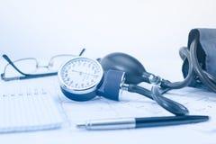 在心脏科医师Tonometer,心电图和笔记薄的工作表上的血压计与笔纪录的 免版税库存图片