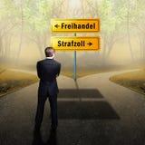 在必须的交叉路的商人身分决定在'自由贸易'和'关税之间'与路标用德语 免版税图库摄影
