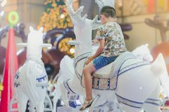 在快活的可爱的亚洲小孩男孩骑马是圆的闹饮 库存图片