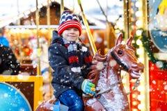 在快活的可爱的小孩男孩骑马努力去做回合转盘马在圣诞节游艺集市或市场,户外 愉快的子项 库存图片