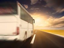 在快速驾驶的白色公共汽车在一条空的柏油路 免版税图库摄影