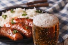 在快餐香肠和sauerk背景的储藏啤酒特写镜头  免版税库存照片
