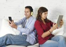 在忽略的长沙发的夫妇使用手机和数字式片剂在互联网瘾 免版税库存图片