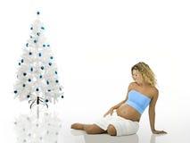 在怀孕的结构树妇女附近的圣诞节 库存照片