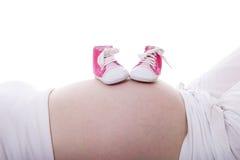 在怀孕的腹部的小的桃红色鞋子 免版税库存图片