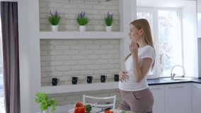 在怀孕,切菜和吃甜椒的美女期间的营养握她的大肚子在厨房里 股票录像
