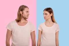 在怒视彼此的米黄T恤杉的年轻夫妇 免版税库存图片
