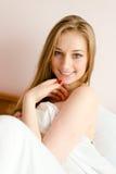 在性感的俏丽的女孩的特写镜头有蓝眼睛和红色钉子的有乐趣愉快的微笑的&看的照相机 免版税库存照片