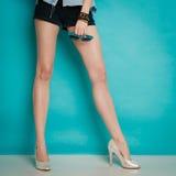 在性感的女性腿的银色高跟鞋时兴的鞋子 图库摄影
