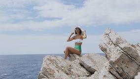 在性感的泳装、太阳镜和草帽打扮的俏丽的深色的妇女坐在背景蓝色海的岩石和 股票视频