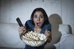 在恐惧的客厅观看的电视覆盖物眼睛的拉丁妇女在家沙发长沙发 免版税库存照片