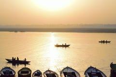 在恒河现出轮廓游船在瓦腊纳西,日出的印度 免版税图库摄影