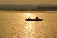 在恒河现出轮廓游船在瓦腊纳西,日出的印度 免版税库存图片