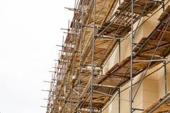 在恢复门面的工作和整修的一个历史建筑附近有木装饰的金属脚手架被修造的 Construc 免版税库存图片