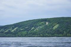 在恶劣天气的河风景 在小山的雷云 免版税库存照片