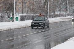 在恶劣天气的街道在冬天 汽车在一条溜滑路驾驶 有暴风雪 免版税库存图片