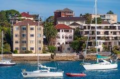 在悉尼港口浇灌前面房子和游艇在停泊处 免版税库存图片